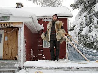 Musher - Conductor de trineo tirado por perros sobre nieve.